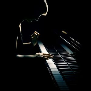 Piano playing pianist concert. Classical music musician player with grand piano in darkness